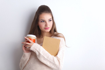 Portrait  a young woman with cup of tea or coffee, holding book