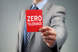 Businessman showing the zero tolerance red card poster