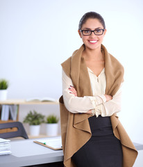 Attractive young businesswoman standing  near desk in office