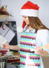 Beautiful woman in santa hat standing at the  kitchen with apron