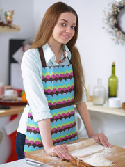 Young woman rolling out dough in the kitchen