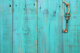 Skeleton key hanging on teal blue wood door