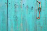 Fototapety Skeleton key hanging on teal blue wood door