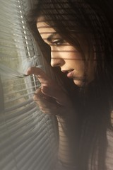Girl spies through the window blinds