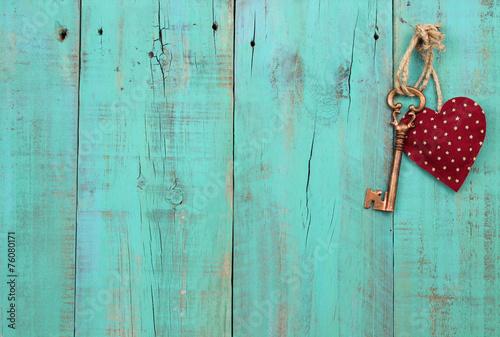 Leinwandbild Motiv Red heart and key hanging on antique wood background