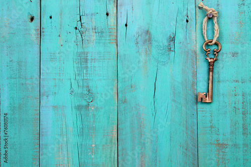 Leinwanddruck Bild Skeleton key hanging on teal blue wood door