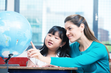 Elementary school teacher explaining Earth globe to asian female