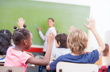 Portrait of children raised their hands in a multi ethnic classr