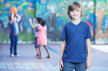 Happy kid smiling in schoolyard with other chilldren playing on