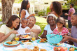 Multi Generation Family Enjoying Meal In Garden Together - 76082969