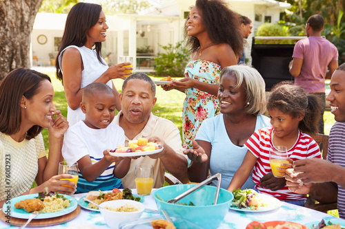 Multi Generation Family Enjoying Meal In Garden Together - 76082923