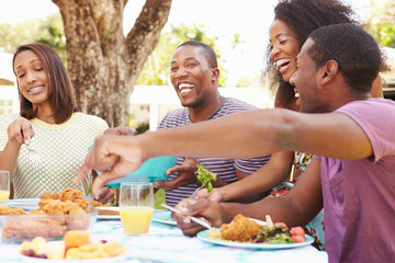 Group Of Friends Enjoying Outdoor Meal At Home