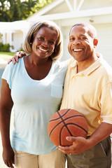 Senior Couple Playing Basketball Together