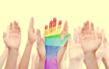 Man's hands painted as the rainbow flag