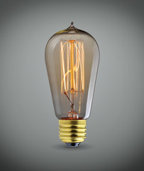 Glowing vintage  light bulb over gray background