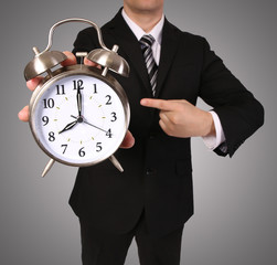 Businessman with Alarm Clock over gray. Time over concept