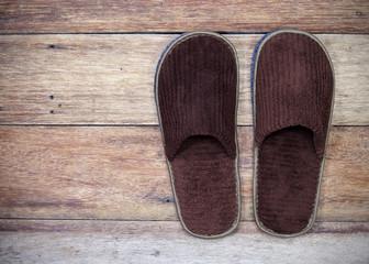 brown home slippers on wood floor