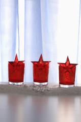 Weihnachtsdekoration mit roten Gläsern und Sterne