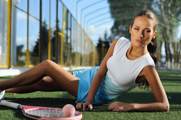 Athletic girl resting after tennis outdoors