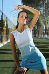 Athletic healthy girl playing tennis outdoors