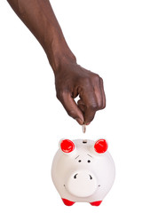 Male hand putting a coin into a piggy bank
