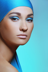 Young woman in turquoise scarf with bright blue makeup