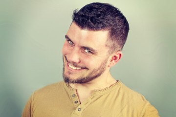 portrait of a smiling young man nervously on a green background