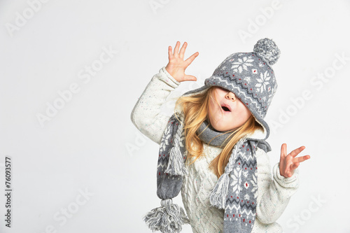 Beautiful blond girl playing in the winter warm hat and scarf on - 76093577