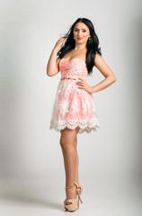 Brunette model posing in cute pastel cocktail dress
