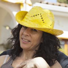 Mujer morena con pelo rizado y sombrero amarillo