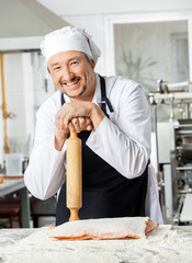Chef Holding Rolling Pin At Counter In Kitchen