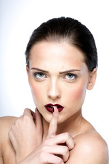 Beauty portrait of attractive woman making a hush gesture