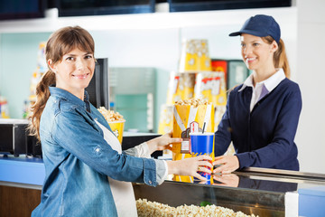 Pregnant Woman Buying Snacks From Seller At Concession Counter