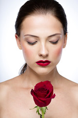 Portrait of a beautiful woman with rose and closed eyes
