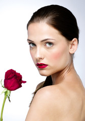 Portrait of attractive woman with perfect skin holding red rose
