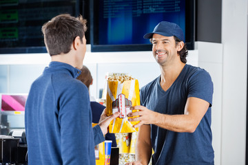 Smiling Seller Giving Popcorn To Man At Concession Stand