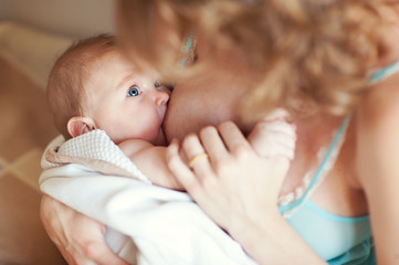 Young european mother breast feeding her newborn baby