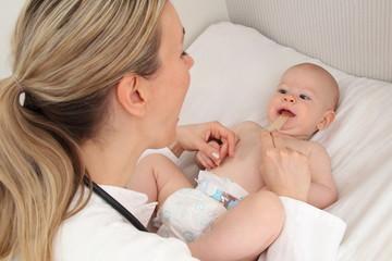 Kinderärztin untersucht Baby mit Mundspatel