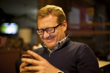 Hombre pelirrojo sonriendo mientras mira el móvil