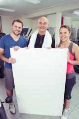 gruppe zeigt ein weißes plakat im fitness-studio