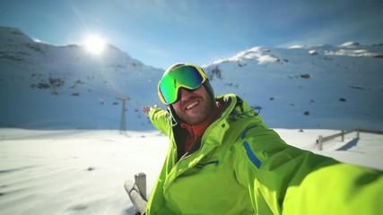 Young man on ski slopes taking a selfie showing landscape