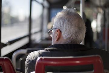 Hombre de pelo cano en autobús