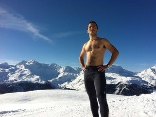 boy shirtless in the mountains with snow