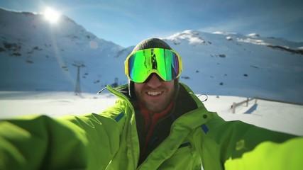 Man on ski slopes taking selfie