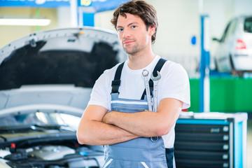 KFZ-Mechaniker arbeitet in Autowerkstatt