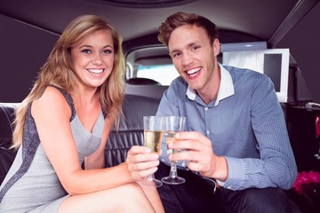Happy couple drinking champagne in limousine