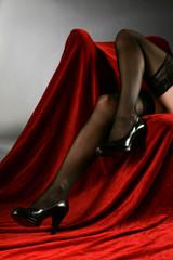 Beine in schwarzen Strümpfen und schwarze Schuhe