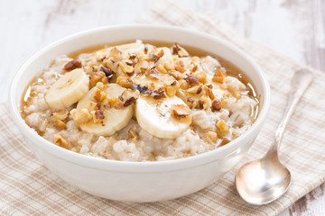 oatmeal with banana, honey and walnuts in bowl