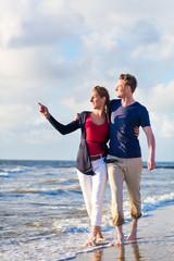 Paar spaziert am Nordsee Strand im Urlaub