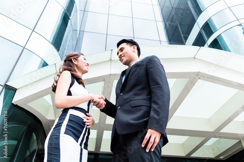 canvas print picture Asian businesspeople handshake in front of high rise building